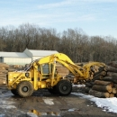 A Crane Picking Up Logs To Feed To The Mill